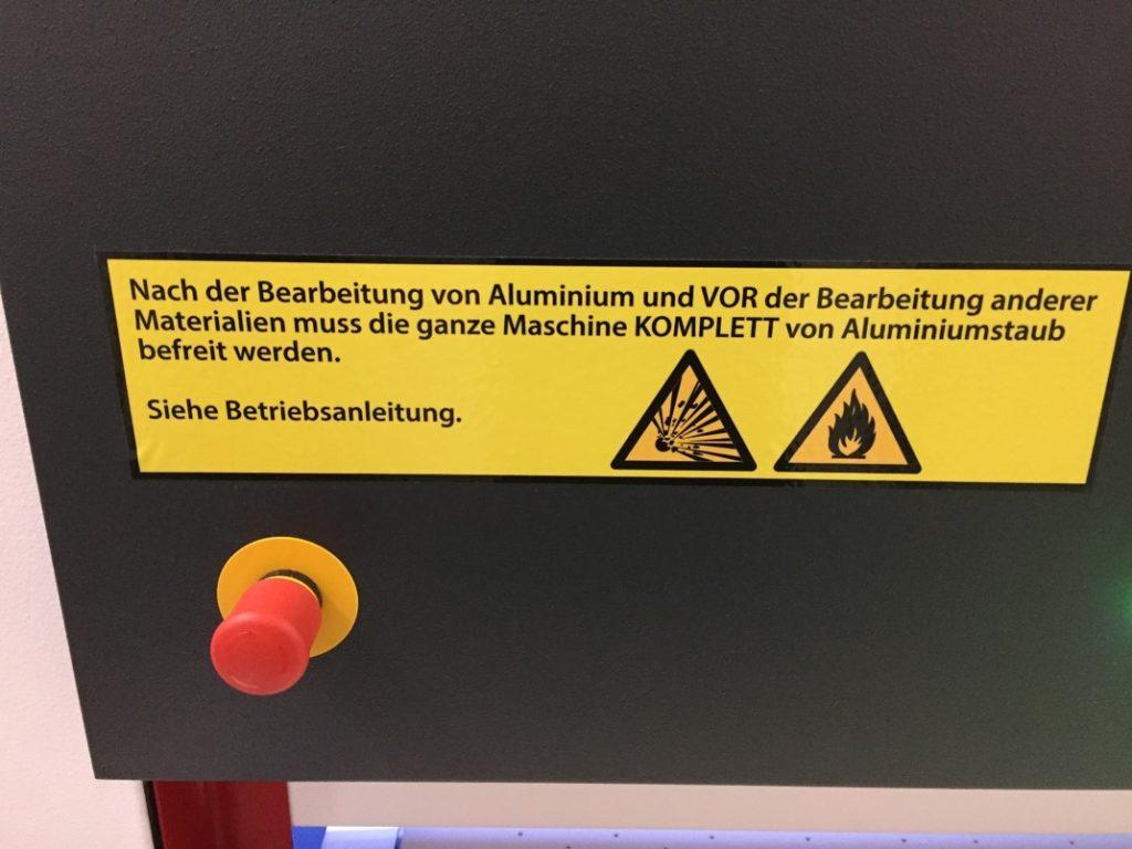 Schild an einer trockenen Entgratmaschine. Aluminiumbearbeitung erfordert besondere Vorsicht!